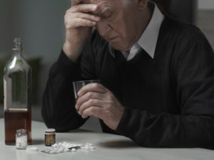 senior_citizen_drinking_and_taking_drugs_looking_depressed